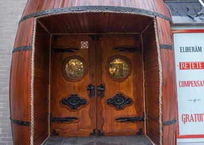amenajare-intrare-in-crama-sub-forma-de-butoi-si-usa-din-lemn-masiv-cu-ornamente-din-fier